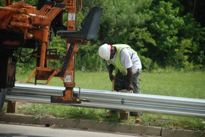 Work crew fixing a guard rail.